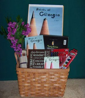Pieces of Georgia basket: signed hardback copy of novel; leather writing journal & pens; colored pencil set w/ storage sac; sketch pad; lilac silk flowers; watercolor paints; poster.